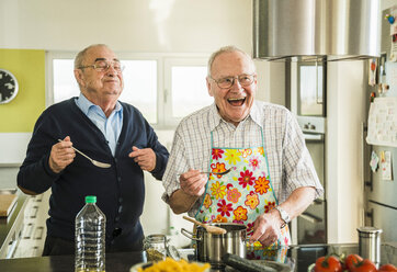 Two happy senior friends cooking in kitchen - UUF003503