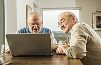 Two senior friends looking at laptop - UUF003548