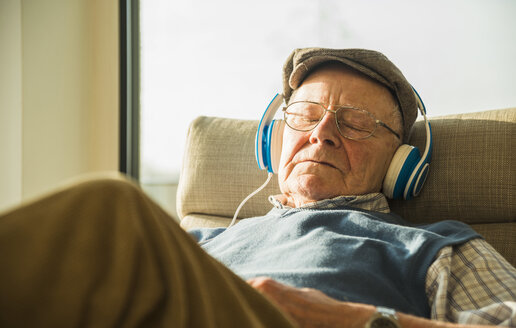 Senior man at home relaxing with headphones - UUF003553