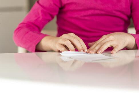 Girl folding piece of paper - JFEF000583