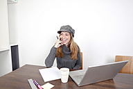 Portrait of smiling woman with laptop sitting at wooden table - PATF000031