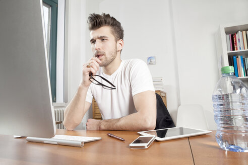 Pensive young man sitting at desk in an office - PATF000044