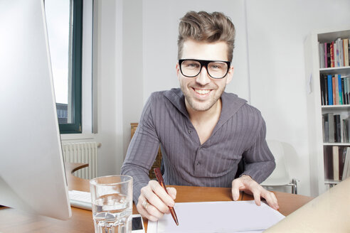 Portrait of smiling young man at desk in an office - PATF000039