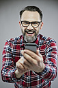 Portrait of excited man looking at smartphone - IPF000202