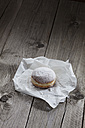 Bismarck doughnut on paper and grey wood - CSF024673