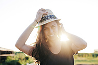 Smiling woman wearing summer hat standing at backlight - BZF000044