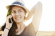 Smiling woman wearing summer hat telephoning with smartphone - BZF000050
