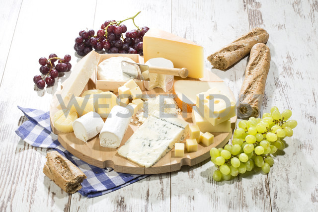 Cheese platter with different sorts of cheese, baguette and grapes on wood - MAEF009869