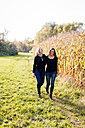 Happy lesbian couple walking along a cornfield - DAWF000300
