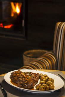 Veal escalope with sauce and champignons on plate, armchair and fireplace in background - AKNF000009