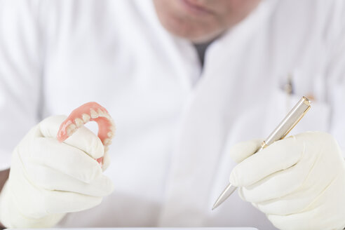 Dental technician examining dentures - DRF001515