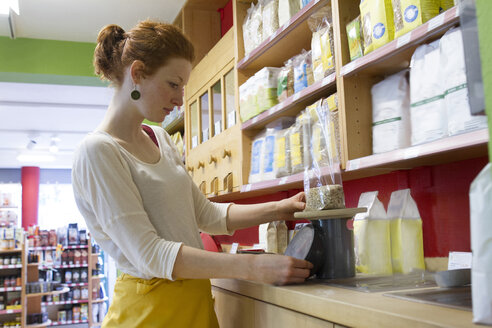 Young woman in wholefood shop weighing granola - SGF001390