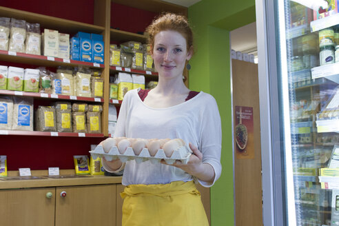 Portrait of smiling young woman in wholefood shop holding palette with fresh eggs - SGF001385