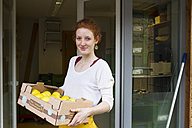 Portrait of smiling young woman with cardboard box of lemons in front of wholefood shop - SGF001386