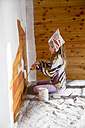 Girl painting wooden wall with paint roller - SARF001438