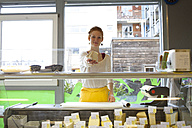 Smiling young woman in wholefood shop giving piece of cheese - SGF001387