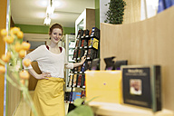Portrait of female shop assistant in wholefood shop - SGF001388