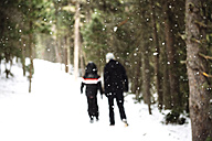 Man and child walking through the forest while snowing - GEMF000081