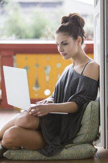Young woman using laptop on balcony - SHKF000288