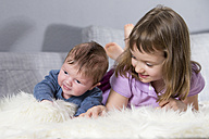 Little girl and newborn brother lying together on sheepskin - ROMF000054