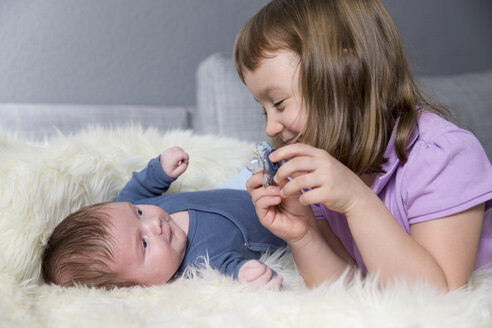 Little girl and newborn brother lying face to face on sheepskin - ROMF000056