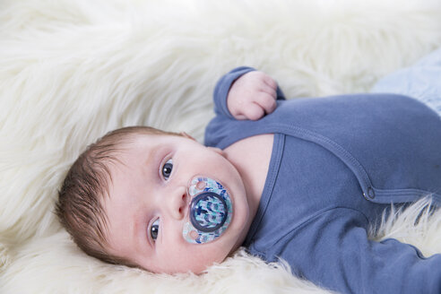 Portrait of newborn baby boy with pacifier lying on sheepskin - ROMF000057