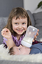 Portarit of happy little girl feeding newborn brother with baby bottle - ROMF000059