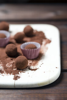 Chocolate truffles and cacao powder on wooden board - MYF000905