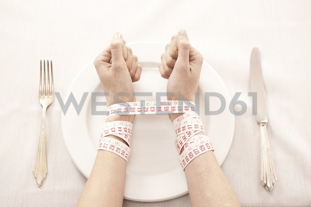 Woman in front of empty plate bound with tape measure - DRF001546 - Stefan Rupp/Westend61