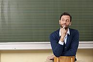 Teacher in classroom at blackboard thinking - MFRF000063