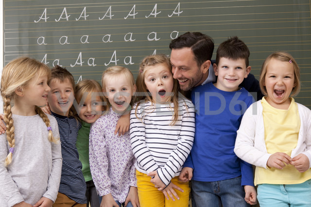 Happy teacher with pupils in classroom - MFRF000113