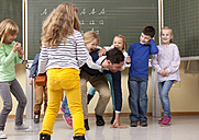 Teacher with playful pupils in classroom - MFRF000116