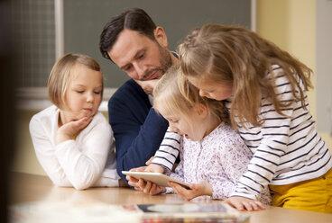 Teacher with schoolgirls using digital tablet in classroom - MFRF000098