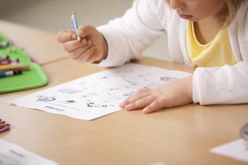 Schoolgirl working on work sheet in classroom - MFRF000101