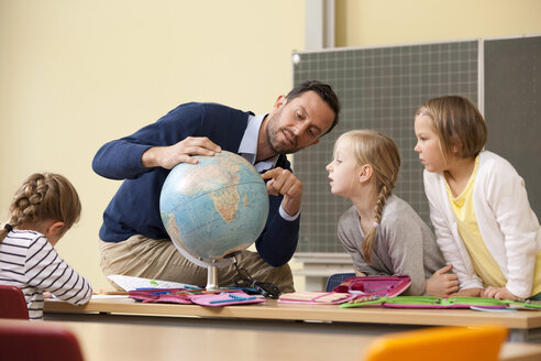 Teacher and pupils looking at globe in classroom - MFRF000130