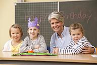 Portrait of teacher and schoolgirls celebrating birthday in classroom - MFRF000141
