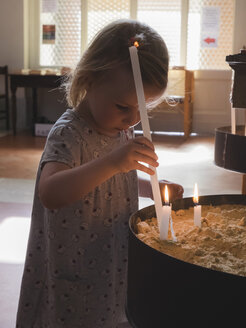 Little girl with candle in a church - GS000979