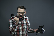 Man screaming into retro telephone in front of grey background - IPF000209