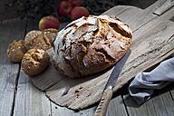 Crusty bread and old bread knife on chopping board, granary rolls - CSF024732
