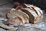 Crusty bread and old bread knife on chopping board - CSF024735
