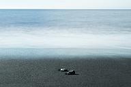 Island, two pebbles lying on dark sandy beach at waterfront - NHF001474