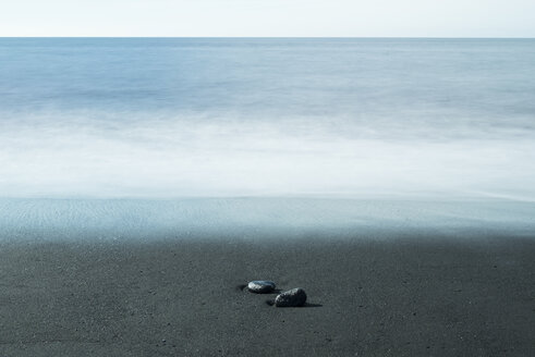 Island, two pebbles lying on dark sandy beach at waterfront - NHF001474