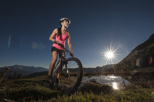 Austria, Altenmarkt-Zauchensee, young woman riding mountain bike at sunrise - HHF005183