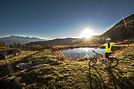 Austria, Altenmarkt-Zauchensee, young woman with mountain bike in the mountains at sunrise - HHF005192