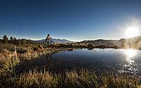 Austria, Altenmarkt-Zauchensee, young woman riding mountain bike at sunrise - HHF005189