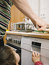 Baby girl watching mother chopping herbs - KRPF001338