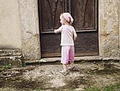 Italy, Tuscany, Montefollonico, girl at wooden door - GSF000988