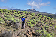 Spain, Canary Islands, La Gomera, Valle Gran Rey, female hiker on hiking trail La Merica, Mountain Fortaleza in the background - SIEF006502