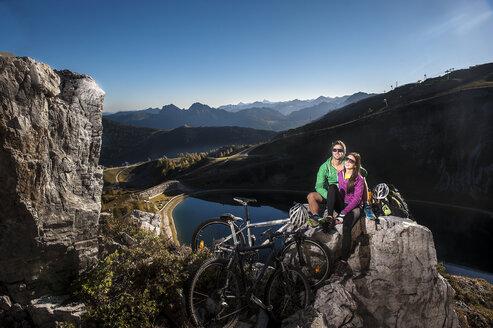 Austria, Altenmarkt-Zauchensee, young couple with mountain bikes in the mountains - HHF005209