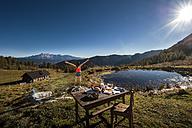 Austria, Altenmarkt-Zauchensee, young woman in the mountains at sunrise - HHF005136